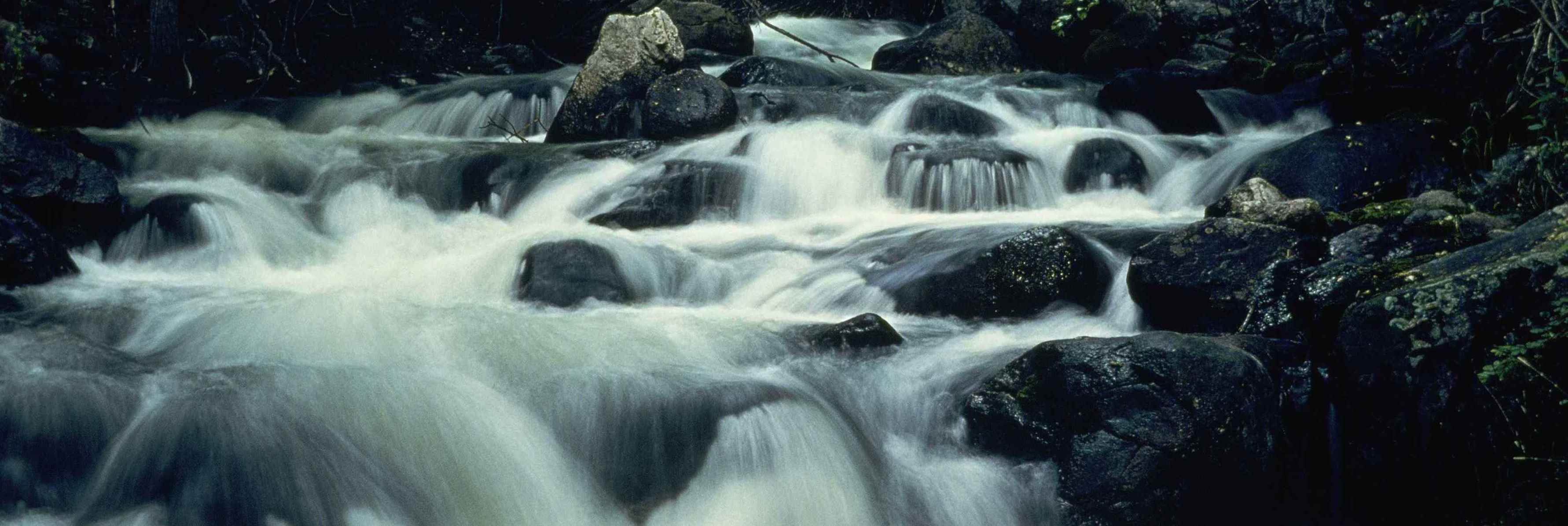 Fast mountain river makes a hazy waterfall / Public Domain